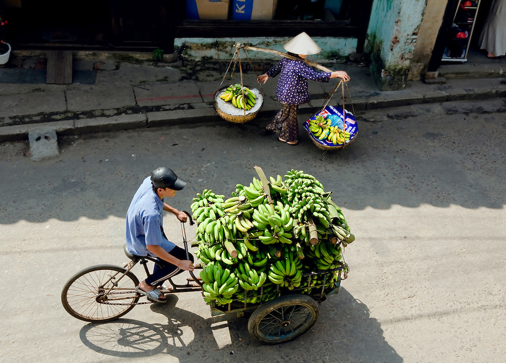 Two modes of banana delivery: man pedals a bicycle cart loaded heavily with green bananas, past a woman carrying a yoke with two pans each with a small bunch of bananas.  Scene viewed from a balcony just above them in the historic town of Hoi An, Vietnam.