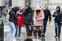 © Licensed to London News Pictures. 16/08/2019. London, UK. Tourists sheltering from the rain in Trafalgar Square on a windy day. The Met Office has issued a severe weather alert for most of today, as almost a month's worth of rain is expected in many parts of the UK. Photo credit: Dinendra Haria/LNP
