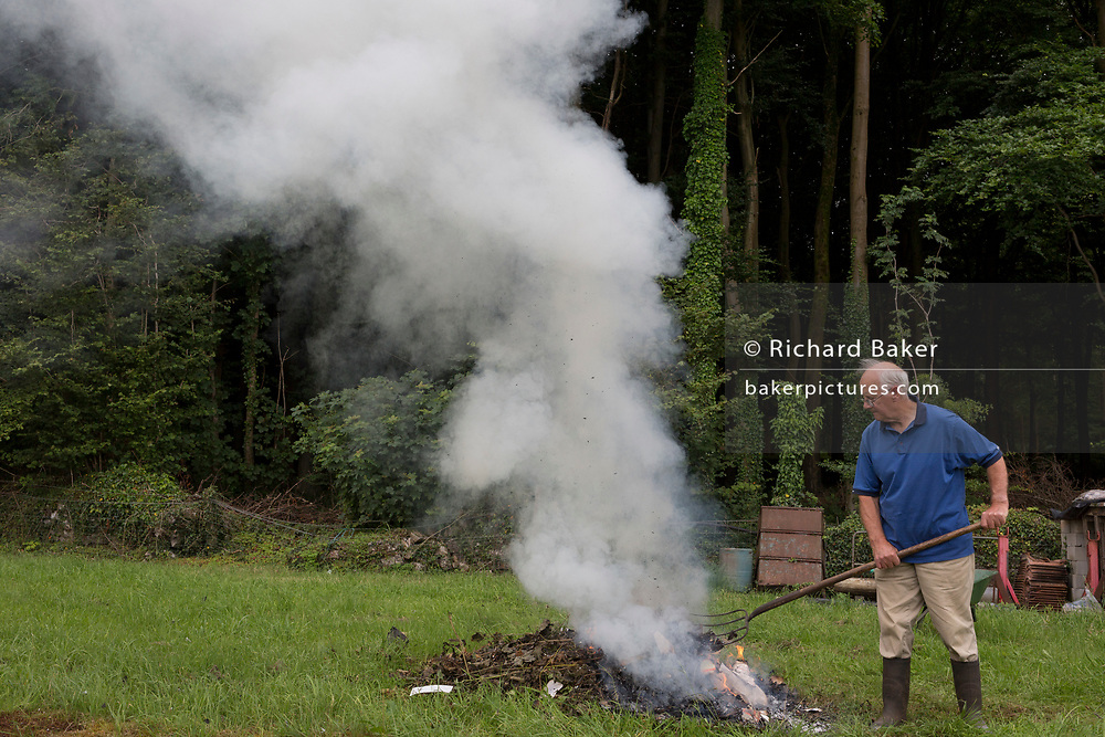 An elderly man burns confidential personal data and accounts paperwork on his land in rural woodland, on 30th July 2017, in Wrington, North Somerset, England.
