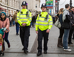 London, December 31 2017. Police in high visibility jackets and numerous anti-terrorism and crowd control measures are in place in the capital ahead of the New Year's Eve fireworks and revelry in central London. PICTURED: Two police officers patrol along the South Bank near the London Eye. © SWNS
