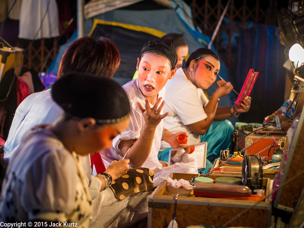 16 JANUARY 2015 - BANGKOK, THAILAND: Performers with the Sai Yong Hong Teochew Opera Troupe chat while they put on their make up before performing at the Chaomae Thapthim Shrine, a Chinese shrine in a working class neighborhood of Bangkok near the Chulalongkorn University campus. The troupe's nine night performance at the shrine is an annual tradition and is the start of the Lunar New Year celebrations in the neighborhood. Lunar New Year, also called Chinese New Year, is officially February 19 this year. Teochew opera is a form of Chinese opera that is popular in Thailand and Malaysia.    PHOTO BY JACK KURTZ