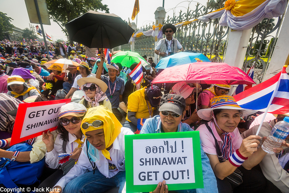 "09 DECEMBER 2013 - BANGKOK, THAILAND: Thai anti-government protestors gather on the sidewalk in front of Government House in Bangkok. Thai Prime Minister Yingluck Shinawatra announced she would dissolve the lower house of the Parliament and call new elections in the face of ongoing anti-government protests in Bangkok. Hundreds of thousands of people flocked to Government House, the office of the Prime Minister, Monday to celebrate the collapse of the government after Yingluck made her announcement. Former Deputy Prime Minister Suthep Thaugsuban, the organizer of the protests, said the protests would continue until the ""Thaksin influence is uprooted from Thailand."" There were no reports of violence in the protests Monday.      PHOTO BY JACK KURTZ"