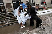 Bride Brenda Khemraj gets help with her dress from her mother Linda, as her groom Steve Caraballo tries to make a path through the snow and slush outside the Newark Courthouse following their wedding on Valentines Day.