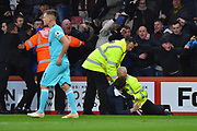 Police and stewards have to hold back celebrating Newcastle fans who invaded the pitch after the injury time equalising goal scored by Matt Ritchie (11) of Newcastle United during the Premier League match between Bournemouth and Newcastle United at the Vitality Stadium, Bournemouth, England on 16 March 2019.