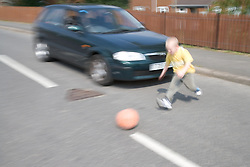 Young boy chasing ball into the road in front of a car,
