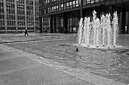 A lone worker clears excess water off Seagram Building plaza along Park Avenue