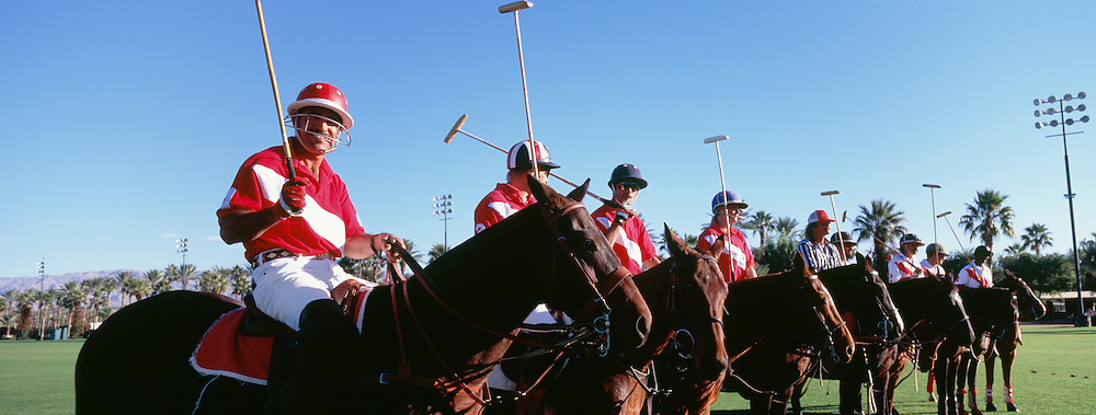 Panoramic shot of polo players and umpire on horses at field