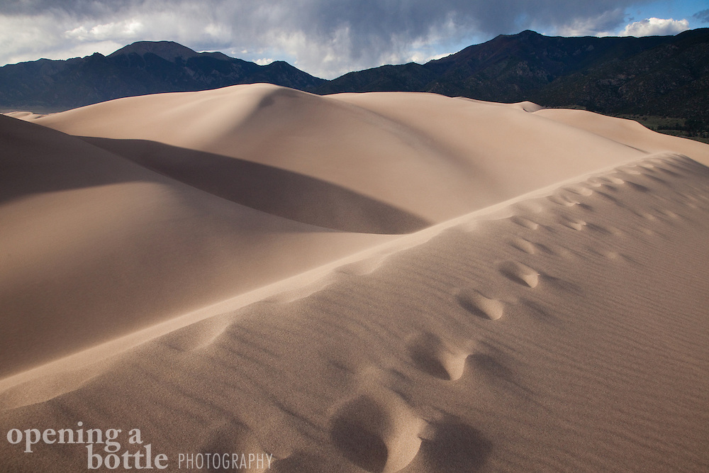 Foot prints cross the ridge tops of the dunes, with Mount Cleveland in the distance, Great Sand Dunes National Park, Colorado.