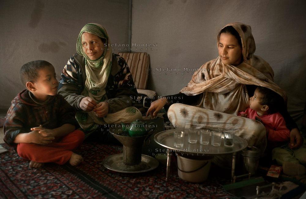 The Saharawi refugee camp  Smara..Sahrawi women with children preparing tea inside the tent.January 2008