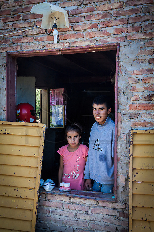 2014/11/22 – Quimili, Argentina: Maite Sousa (12), Franco David Sousa (14) at the window of their house in in the allotment number 5 of the Guaycurú Indigenous Community. A few weeks before armed men belonging to soy groups forced entry and threaten them when they were alone in the house with a friend. The men force them to take a few valuable belongings while they destroyed other material stuff and told them to never come back. Due to the help of neighbours of the community the family was able to scare the men away and recover their house. (Eduardo Leal)