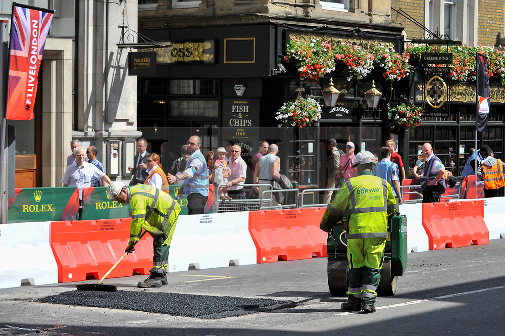 © Licensed to London News Pictures. 12/07/2017. London, UK. Workers resurface Whitehall ahead of the Formula One Car parade.  Formula One racing comes to Trafalgar Square and Whitehall for a promotional event called F1LiveLondon ahead of the British Grand Prix at Silverstone. Photo credit : Stephen Chung/LNP