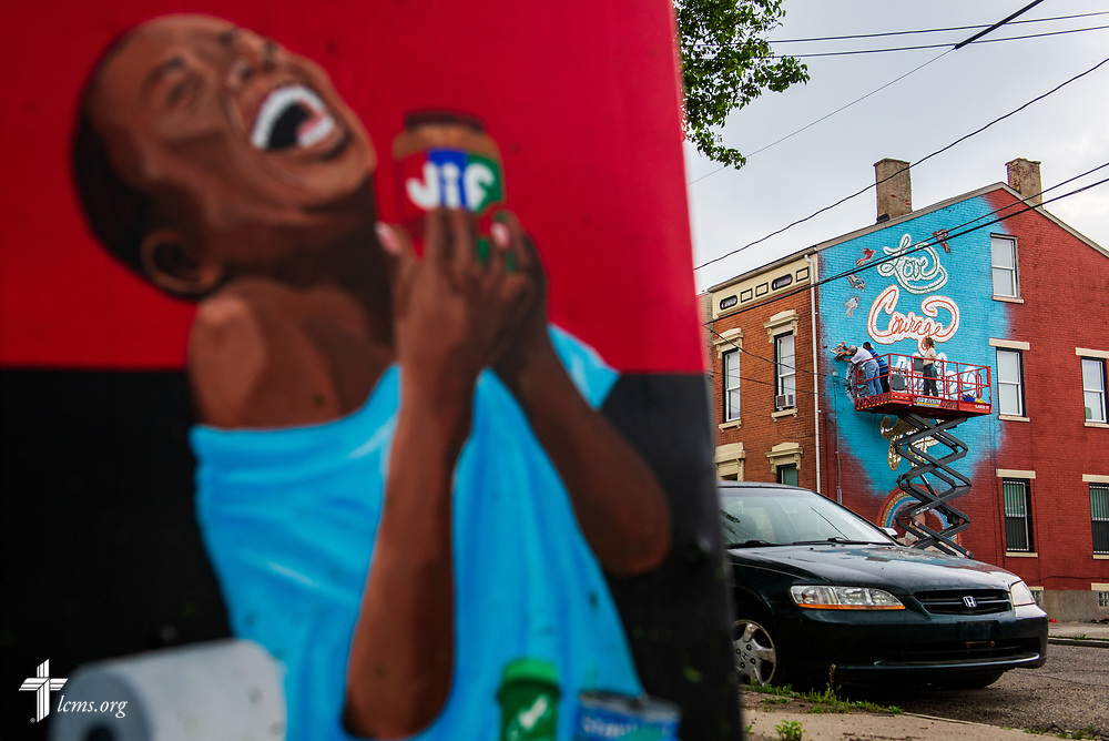Artist Rachel Ziegler, volunteer Martha Gitt and Curtis Jones from Prince of Peace Lutheran Church in the Over-the-Rhine neighborhood of Cincinnati, work on a new mural on the side of Victoria's House of Hope, a transitional housing apartment building that is part of The Welcome Home Collaborative program, on Wednesday, May 16, 2018, in Cincinnati. Victoria, a young woman who volunteered her time at Prince of Peace Lutheran Church, made a wish to the Make-a-Wish Foundation to rehab the old building before she died of a brain tumor. Ziegler designed the mural and had attendees of the church and external community assist with the construction. LCMS Communications/Erik M. Lunsford