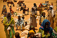 Women wait to receive weekly rations from a CARE International food distribution point in Iridimi refugee camp near Iriba, in eastern Chad.
