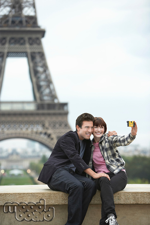 France Paris couple taking self portrait  in front of Eiffel Tower