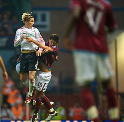 LONDON, ENGLAND - Saturday, September 19, 2009: Liverpool's Fernando Torres rises above West Ham United's James Tomkins to score the third goal with a header, his second goal of the game, to seal a 3-2 victory during the Premiership match at Upton Park. (Pic by David Rawcliffe/Propaganda)
