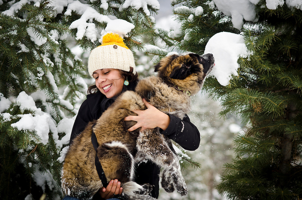 A young twenty something latina woman playing with her young dog in the Colorado snow.