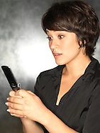 Hispanic woman (20-30) with mobile phone.
