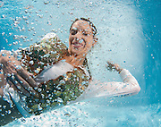 A young trendy dressed woman floats underwater in air bubbles Model release available