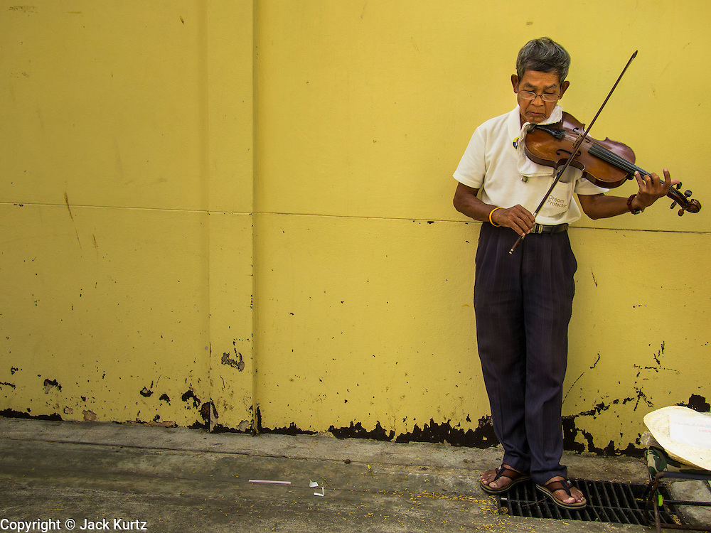 12 DECEMBER 2013 - BANGKOK, THAILAND: A man plays violin in a corner of Wat Bowon Niwet in Bangkok during a mourning service for the Supreme Patriarch of Thailand. Somdet Phra Nyanasamvara, who headed Thailand's order of Buddhist monks for more than two decades and was known as the Supreme Patriarch, died Oct. 24 at a hospital in Bangkok. He was 100. He was ordained as a Buddhist monk in 1933 and rose through the monastic ranks to become the Supreme Patriarch in 1989. He was the spiritual advisor to Bhumibol Adulyadej, the King of Thailand when the King served as monk in 1956. There is a 100 day mourning period for the Patriarch, the service Thursday, on the 50th day, included members of the Thai Royal Family. Although the Patriarch was a Theravada Buddhist, he was the Supreme Patriarch of all Buddhists in Thailand, including the Mahayana sect, which is based in Chinese Buddhism.     PHOTO BY JACK KURTZ