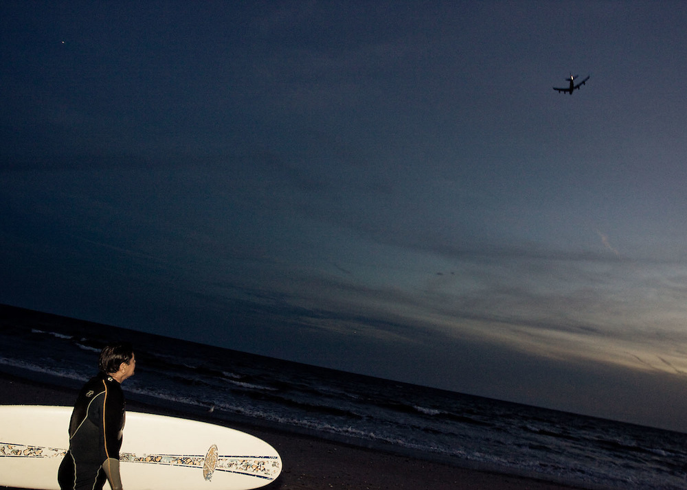 A surfer watches a jet fly over the 91st Street surf break, Rockaway Beach, Queens, NY.