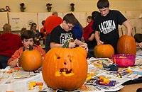 Close to 400 pumpkins are being carved by Laconia Middle School students on Wednesday morning to contribute to the Tower at Pumpkin Fest on Saturday.  (Karen Bobotas/for the Laconia Daily Sun)