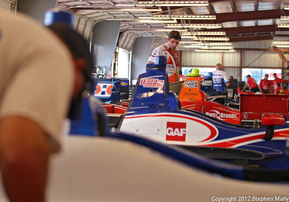 Workers prepare cars in the garage before the start of the IZOD IndyCar Iowa Corn Indy 250 auto race at the Iowa Speedway in Newton, Iowa on Saturday, June 23, 2012.