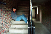 Bored teenage boy sitting on the stairs in housing estate Lambeth Walk South London c.2000