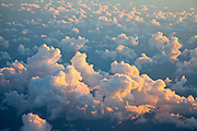 Aerial of a sunset illuminating cumulus clouds