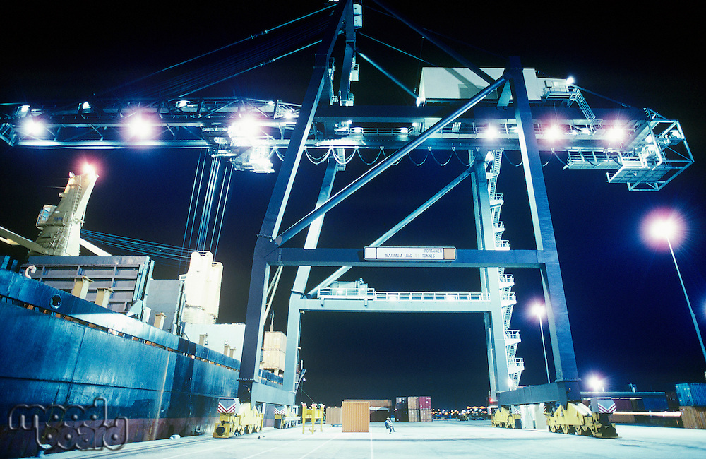 Crane loading container ship at night