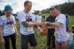 © Licensed to London News Pictures. 06/03/2016. Dorking, UK. Competitors being presented with a prize of beer after taking part in the 2016 Wife Carrying Race in Dorking, Surrey.  The race, which is run over a course of 380m, with both men and women carry a 'wife' over obstacles,  is believed to have originated in the UK over twelve centuries ago when Viking raiders rampaged into the northeast coast of  England carrying off any unwilling local women .  Photo credit: Ben Cawthra/LNP