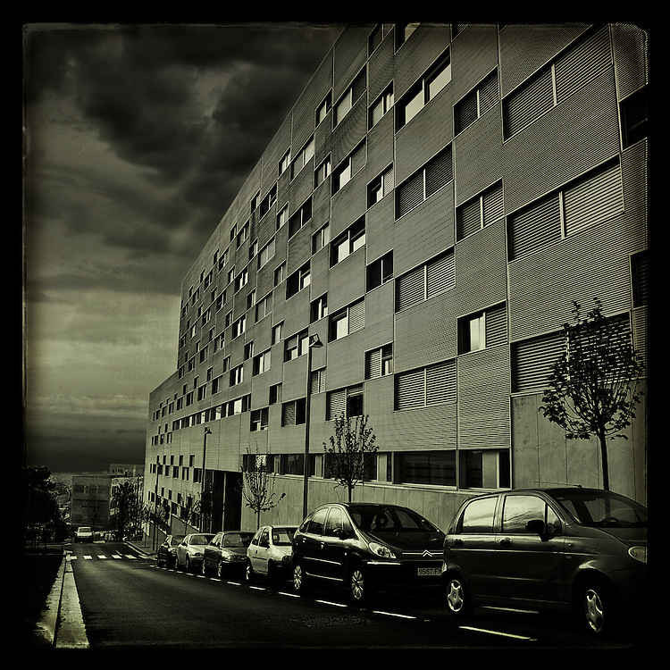 A dramatic view of a block of flats with cars
