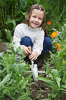 Girl (5-6) gardening portrait