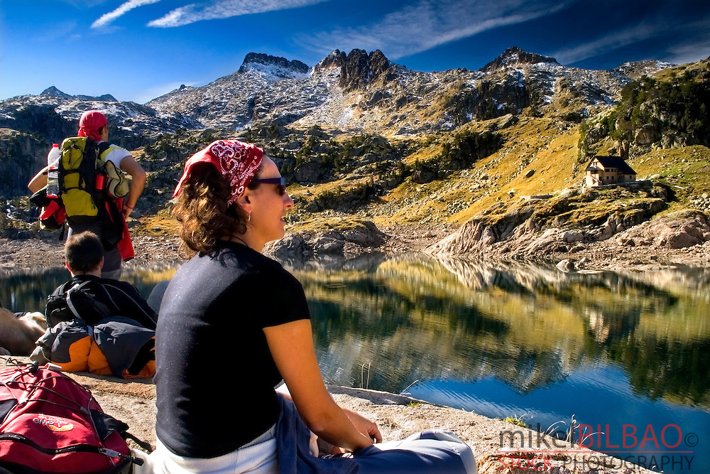 people near the Bigger Lake of Colomer and Colomer I mountain hut. Colomers glaciar cirque. Aran Valley. Pyrenees mountain range. Lerida province.  Catalonia, Spain, Europe.