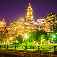Boston skyline at night with Christopher Columbus Waterfront Park, Custom House Tower clock and downtown Boston buildings.