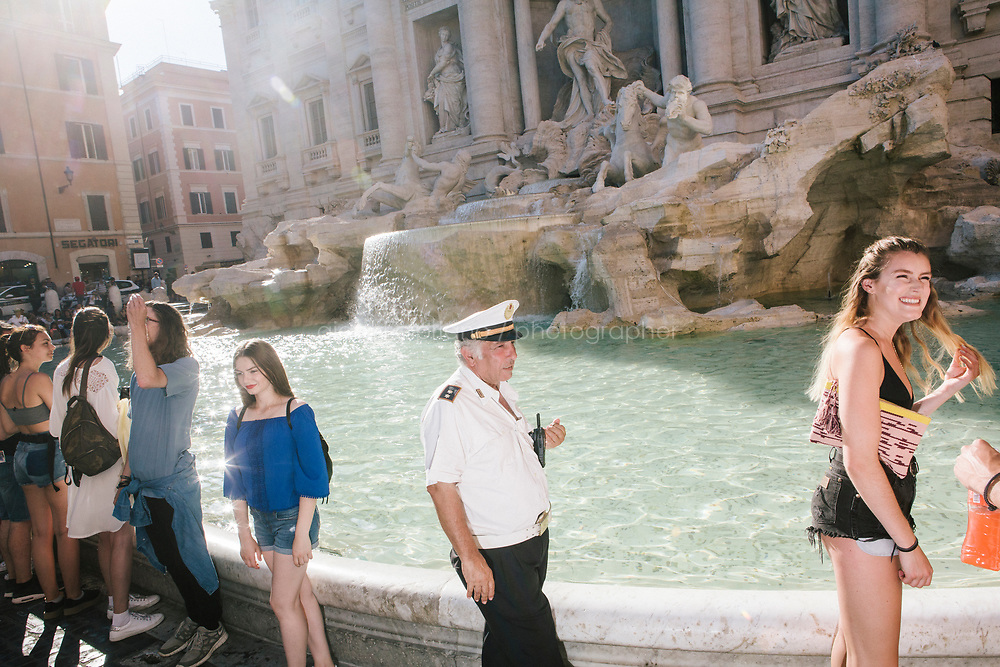 ROME, ITALY - 20 JUNE 2017: A Roman policeman, entrusted to protect the Fountain of Trevi, is seen here by the fountain in Rome, Italy, on June 20th 2017.<br /> <br /> The warm weather has brought a menacing whiff of tourists behaving badly in Rome. On April 12, a man went skinny-dipping in the Trevi fountain resulting in a viral web video and a 500 euro fine.<br /> <br /> Virginia Raggi, the mayor of Rome and a national figurehead of the anti-establishment Five Star Movement,  issued an ordinance involving harsher fines for eating, drinking or sitting on the fountains, for washing animals or clothes in the fountain water or for throwing anything other than coins into the water of the Trevi Fountain, Bernini&rsquo;s Four Fountains and 35 other city fountains of artistic or historic significance around the city.  &ldquo;It is unacceptable that someone use them to go swimming or clean themselves, it&rsquo;s an historic patrimony that we must safeguard,&rdquo; Ms. Raggi said.