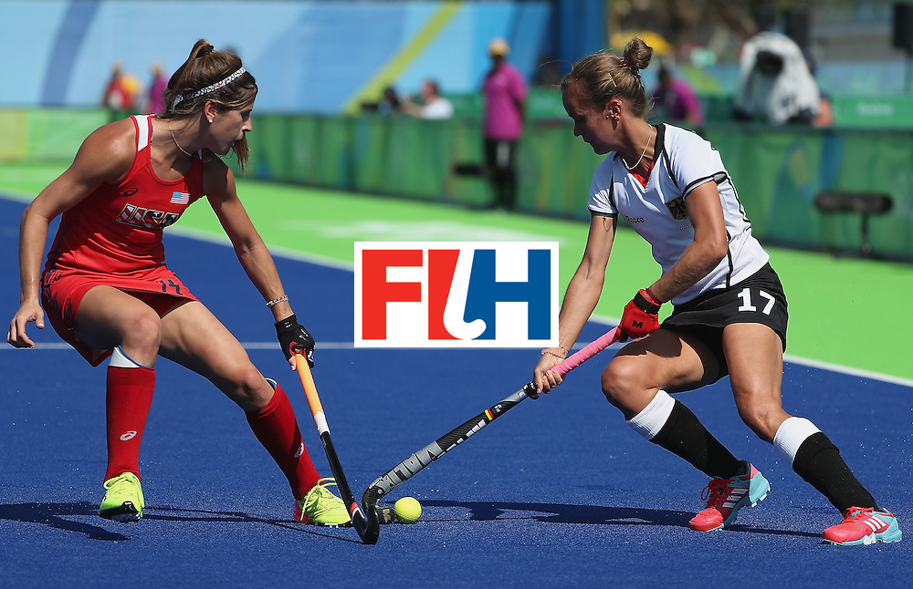 RIO DE JANEIRO, BRAZIL - AUGUST 15: Jana Teschke #17 of Germany moves the ball against Katie Reinprecht #14 of United States  during the quarter final hockey game on Day 10 of the Rio 2016 Olympic Games at the Olympic Hockey Centre on August 15, 2016 in Rio de Janeiro, Brazil.  (Photo by Christian Petersen/Getty Images)