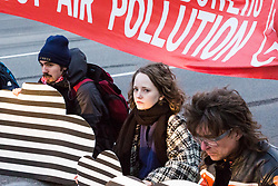 PICTURED: Anti-pollution protesters sit on Oxford Street at Marble arch causing huge traffic tailbacks. Demonstrators from the anti-pollution group Stop Killing Londoners cause traffic chaos for London commuters as they conduct a series of short roadblocks at Marble Arch stopping cars and buses from entering Oxford Street and Park Lane. Irate motorists accused them of creating more pollution than they were stopping, whilst the group said their objectives were long term. A leaflet handed out to motorists says the government is not doing enough to tackle the crisis costing 'taxpayers and the NHS £billions [sic] a year'. PLACE, January 29 2018. © Paul Davey