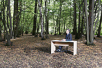 Business man sitting at desk in middle of forest thinking