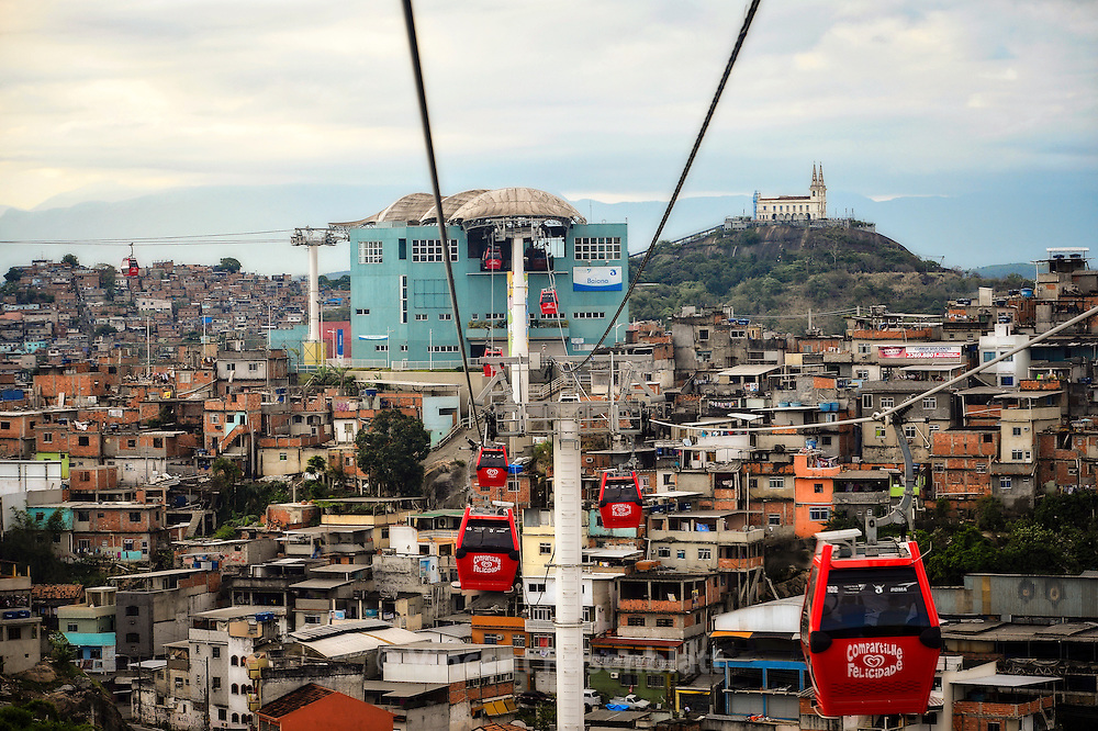 Cable Car connecting all hills and favelas of the Complexo do Alemão. One dollar for the most amazing urban landscapes from Zona Norte of Rio de Janeiro. In the background, the Penha Church - sanctuary.