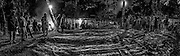 Lors de cette dernière cérémonie coutumière, le clan du père (ici à droite) remet le « souffle de la vie » de l'être décédé et demande pardon pour le non-maintien de celle-ci à ses oncles maternels (à gauche) qui lui avaient insufflé à la naissance. Le don est supérieur à celui fait précédemment par les oncles maternels et est complété par un sac comprenant tous les effets personnels du défunt (sac noir au pied du cocotier). Les pièces d'étoffes sont étendues au sol en signe du lien entre les clans qui se poursuivra malgré la mort.<br /> Tribu de Tendo - Hienghène - Nouvelle Calédonie - Aout 2013