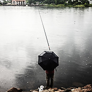 A man fishing in the estonian side of Narva river, that fix the border between Estonia and Russia