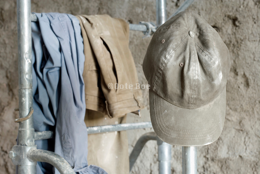 clothing and cap hanging on a platform in a house being renovated