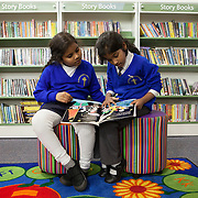 """Southall, Greater London, UK, January 27, 2015. <br /> <br /> At the """"Dominion Centre & Library"""", in Southall, two schoolgirls, an Indian and a Srilankan, read a book together after school. Change comes from education. Young Indian girls are eager to learn, proud to be successful in school."""
