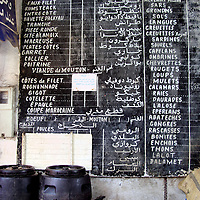 Menu Chalk Board at Old Medina in Casablanca, Morocco<br /> This chalk board menu at the Old Medina is in French and Arabic. This multilingual approach reflects the mixed heritage of Morocco&rsquo;s largest city.  Casablanca is an old, dirty city on the North Atlantic coast of Africa. It was first settled by the Berbers around the 7th century BC. During the early half of the 20th century, the country was under French rule.