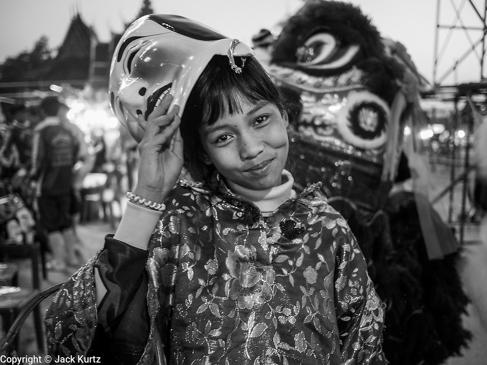 "14 MARCH 2014 - NAKHON CHAI SI, NAKHON PATHOM, THAILAND: A member of a lion dance troupe waits to perform during the tattoo festival at Wat Bang Phra. Wat Bang Phra is the best known ""Sak Yant"" tattoo temple in Thailand. It's located in Nakhon Pathom province, about 40 miles from Bangkok. The tattoos are given with hollow stainless steel needles and are thought to possess magical powers of protection. The tattoos, which are given by Buddhist monks, are popular with soldiers, policeman and gangsters, people who generally live in harm's way. The tattoo must be activated to remain powerful and the annual Wai Khru Ceremony (tattoo festival) at the temple draws thousands of devotees who come to the temple to activate or renew the tattoos. People go into trance like states and then assume the personality of their tattoo, so people with tiger tattoos assume the personality of a tiger, people with monkey tattoos take on the personality of a monkey and so on. In recent years the tattoo festival has become popular with tourists who make the trip to Nakorn Pathom province to see a side of ""exotic"" Thailand.   PHOTO BY JACK KURTZ"
