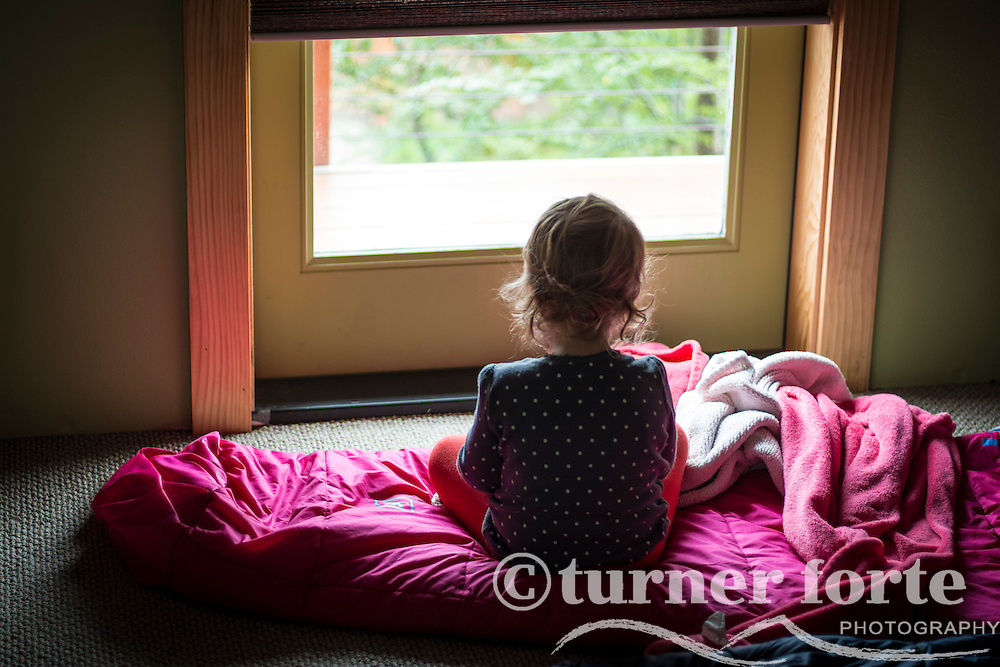 Toddler girl sits on sleeping bag looking out window in Portland, Oregon.
