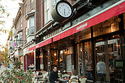 A couple sits at an outside table at Kalendar, a café on College Street in Toronto's Little Italy neighborhood.
