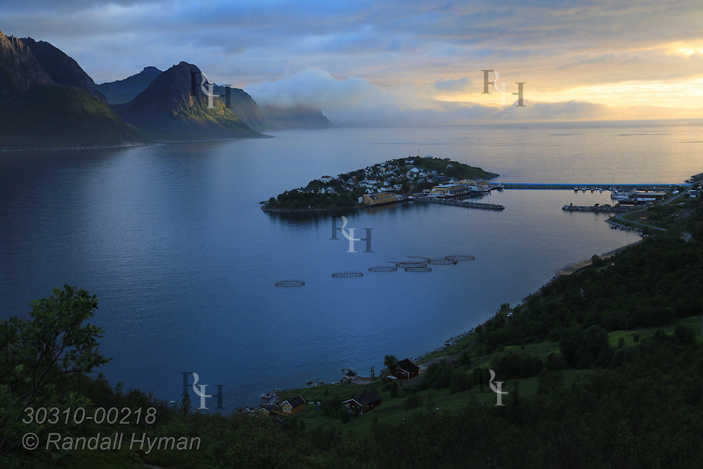 Midnight sun pierces through stormy skies in wee hours of a bright summer night above rugged fjord mountains and island town of Husoy along National Tourist Route on Senja Island, Norway.