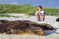A young girl photographing a Galapagos Sea Lion, Zalophus wollebacki on Cerro Brujo, San Cristobal Island, Galapagos National Park and Marine Reserve, Ecuador.