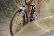 mountain biker riding through the mud and water during a race